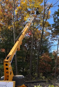 Photo of Ted Reimann, W1OG, in the 2.5 ton bucket lift for tree work to put up the new 80-meter dipole