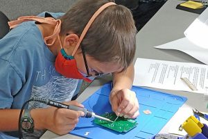 photo of Tate Aldridge, K1MKD, soldering a circuit board